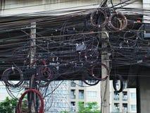 Líneas eléctricas y telefónicas sucias en polos Fotografía de archivo libre de regalías
