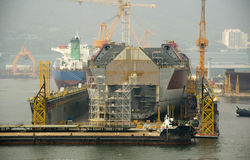 LNG tanker in shipyard. New building LNG tanker in dry dock with cranes on background Stock Photos