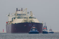 LNG TANKER AND  TUGS. Tanker entering the port by tugboats assisted on a rope Royalty Free Stock Images