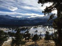 Långa skuggor och moln över korkade bergmaxima för snö Arkivfoto