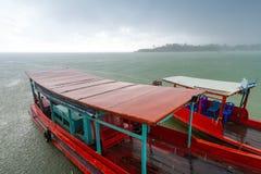Långa svanfartyg på floden på skurkrollen regnar Royaltyfri Bild