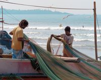 Loсal fishermen stand on boat and untangle, range fishing net, in background ocean beach. stock photography