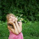 Lo ia della ragazza che si siede nell'erba e nel sogno Fotografie Stock