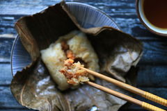 Lo Mai Gai. A small chunk of unwrapped lo mai gai being picked-up with a pair of chopsticks then lifted high; with focus on the lifted chunk and leaving the rest royalty free stock images