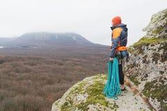 lo Pantaloni a vita bassa-scalatore sta in un piumino su una roccia con una corda sulla sua spalla Immagini Stock