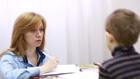 Lo psicologo sta esaminando il ragazzo Bambino di consiglio psicologico archivi video