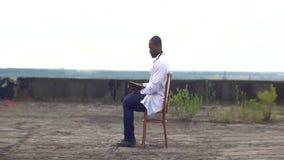 Lo psicoterapeuta africano sicuro sta riposando con il libro sul tetto di vecchio ospedale rovinato archivi video