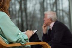 Lo psicoterapeuta ascolta il suo cliente fotografie stock