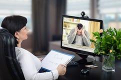 Lo psicoterapeuta online intende aiutare all'uomo depresso Fotografia Stock