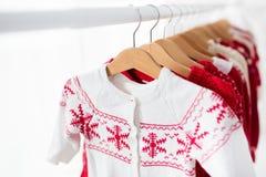 Lo scaffale dei vestiti con il Natale rosso tricotta l'usura Immagine Stock Libera da Diritti