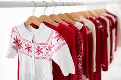 Lo scaffale dei vestiti con il Natale rosso tricotta l'usura Immagini Stock Libere da Diritti