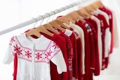 Lo scaffale dei vestiti con il Natale rosso tricotta l'usura Fotografia Stock Libera da Diritti