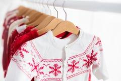Lo scaffale dei vestiti con il Natale rosso tricotta l'usura Fotografia Stock