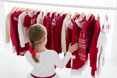 Lo scaffale dei vestiti con il Natale rosso tricotta l'usura Immagini Stock