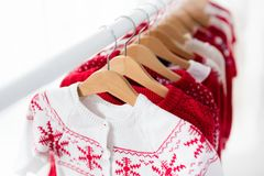 Lo scaffale dei vestiti con il Natale rosso tricotta l'usura Immagine Stock