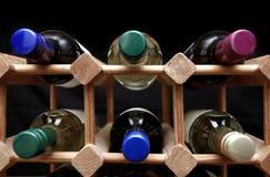 Lo scaffale di legno del vino con la varia bottiglia di colore completa sul backgro nero Immagini Stock Libere da Diritti