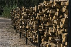 Lo scaffale lungo impilato con legna da ardere ha tagliato per i camini Immagine Stock