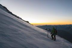 Lo scalatore al primo mattino dell'alba cammina sul pendio e sulla terra sopra la neve spazza lo scaccianeve Fotografia Stock
