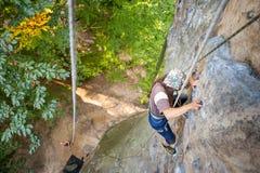 Lo scalatore della donna sta scalando su una parete rocciosa Fotografia Stock