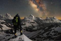 Lo scalatore della foto di notte sta sopra una montagna nella neve ed esamina le montagne circostanti sopra cui lo stellato Fotografia Stock Libera da Diritti