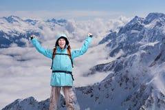 Lo scalatore di montagna maschio felice con le armi si è alzato sopra la testa nei precedenti le alte montagne Immagine Stock Libera da Diritti