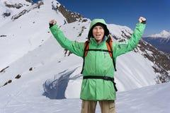 Lo scalatore di montagna maschio felice con le armi si è alzato sopra la testa nei precedenti le alte montagne Immagine Stock