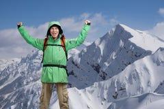 Lo scalatore di montagna maschio felice con le armi si è alzato sopra la testa nei precedenti le alte montagne Fotografia Stock