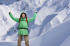 Lo scalatore di montagna maschio felice con le armi si è alzato sopra la testa nei precedenti le alte montagne Fotografie Stock Libere da Diritti