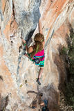 Lo scalatore femminile che prova a tenere la tenuta nell'ultimo sforzo per evitare profondo cade Fotografia Stock Libera da Diritti