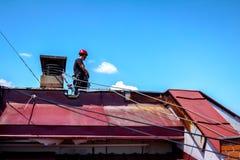 Lo scalatore industriale sta limitando le sue corde al camino fatto di Fotografie Stock