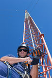 Lo scalatore mette l'attrezzatura di sicurezza prima di scalata della torre fotografia stock libera da diritti
