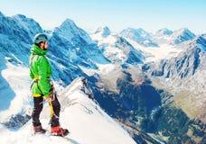 Lo scalatore raggiunge la sommità del picco di montagna Successo, libertà a immagini stock