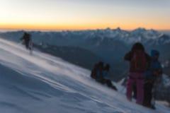 Lo scalatore vago al primo mattino dell'alba cammina sul pendio e sulla terra sopra la neve spazza lo scaccianeve Fotografia Stock