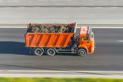 Lo scarico del camion con un carico di suolo nel corpo guida all'alta velocità sulla strada principale Immagini Stock