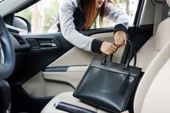 Lo scassinatore della donna ruba una borsa a tracolla attraverso la finestra della t automobilistica Fotografia Stock