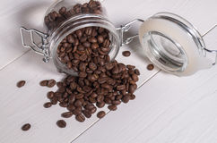 Lo scattering del caffè espresso dei chicchi di caffè delle banche trasparenti Fotografia Stock Libera da Diritti