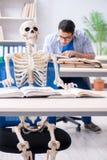 Lo scheletro dello studente che ascolta la conferenza in aula Immagine Stock