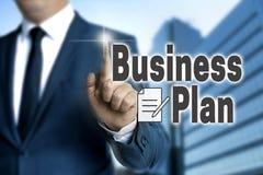 Lo schermo attivabile al tatto del business plan è azionato dall'uomo d'affari immagini stock