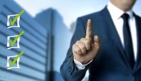 Lo schermo attivabile al tatto della lista di controllo è indicato dall'uomo d'affari Immagini Stock