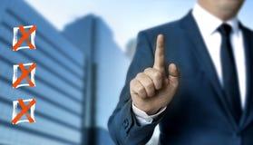 Lo schermo attivabile al tatto della lista di controllo è indicato dall'uomo d'affari Immagine Stock