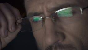 Lo schermo del computer portatile con gli archivi ha riflesso in vetri, agente investigativo che lavora alla notte stock footage