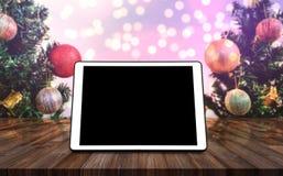 Lo schermo del nero dello spazio in bianco della compressa di Digital, sullo scrittorio di legno con l'albero di Natale, Bokeh va Immagini Stock
