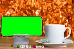 Lo schermo verde in bianco sul telefono cellulare ed il legno tagliano fotografia stock