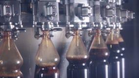 Lo schiocco e la soda, bevanda gassosa che versa in bottiglie sulle bevande fresche hanno automatizzato il trasportatore stock footage