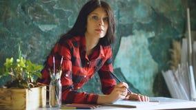 Lo schizzo della pittura dell'artista della giovane donna sul taccuino di carta con la matita e esamina la macchina fotografica immagine stock libera da diritti
