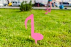 Lo schizzo delle note rosa musicali sopra il prato inglese verde Fotografia Stock