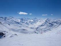 Lo sci pende in pieno di neve circondata dai picchi ripidi Fotografia Stock