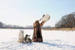 Lo sciamano nordico batte il tamburino che esegue le chiamate di un rito balza Cani del husky Paesaggio di inverno fotografia stock