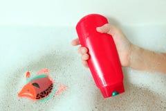 Lo sciampo della tenuta della mano del bambino imbottiglia il bagno del sapone Fotografie Stock Libere da Diritti