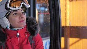 Lo sciatore adorabile sorridente della donna del primo piano aumenta sedendosi in Ski Lift Cable Car stock footage